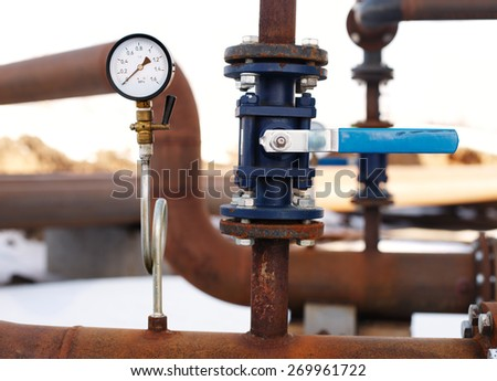 blue valve and manometer on rusty pipe close up - stock photo