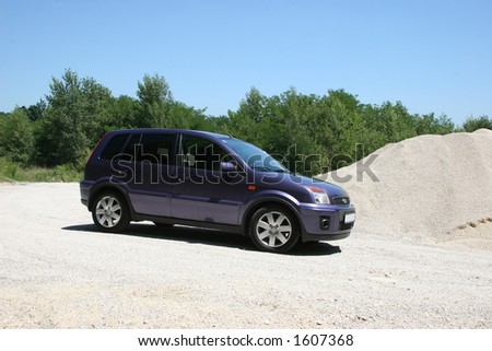blue van in sandy surroundings
