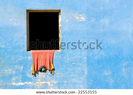 Blue vintage wall with red t-shirt hanging out of window in colonial town Baracoa on Cuba - stock photo