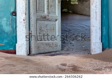 Blue wall and door of abandoned house in sand. Shot in Kolmanskop ghost town, Namibia. - stock photo