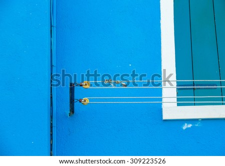 Blue wall with blue pipiline and washing line detail, located in Island Burano, near Venice - stock photo