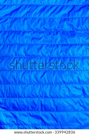 blue warm insulated texture of jacket,warm light weight  insulated  jacket  on white background. - stock photo
