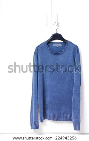 Blue Warm Long Sleeve Shirt on Black Hanger Hang on White Closet Door - stock photo