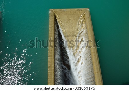 Blue water are falling through the concrete flume in the artificial reservoir of the hydroelectric power station. - stock photo