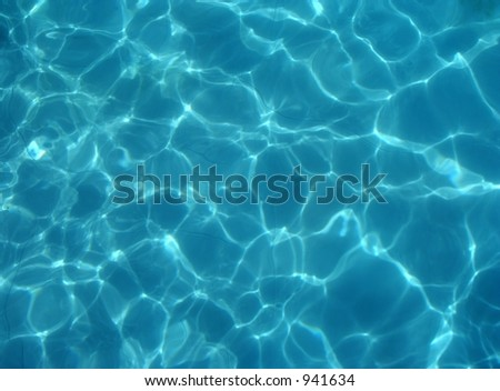 Blue water background from swimming pool with light reflections