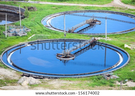 Blue water in an industrial wastewater treatment circular settlers - stock photo
