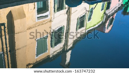 Blue water of Burano canal with colorful buildings reflected.