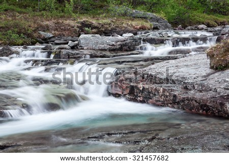Blue water of mountain river flowing from the peaks, long exposure - stock photo