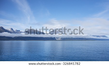 Blue water of the Lynn Canal near Glacier Point with low clouds and blue sky as seen from a boat. - stock photo