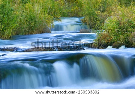 Blue water on cascade of river - stock photo