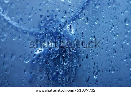 Blue water on glass shower door with bubbles as a background. - stock photo
