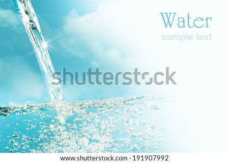 Blue water splash isolated on sky background  - stock photo