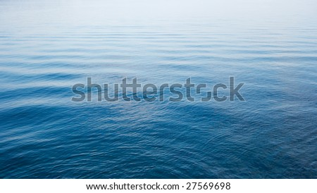 Blue water surface with small waves - stock photo