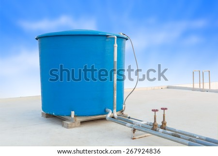 Blue water tank of industrial building on roof top or deck and blue cloud sky background - stock photo