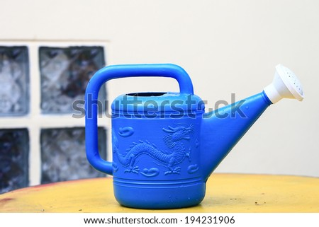 blue watering can in garden. - stock photo