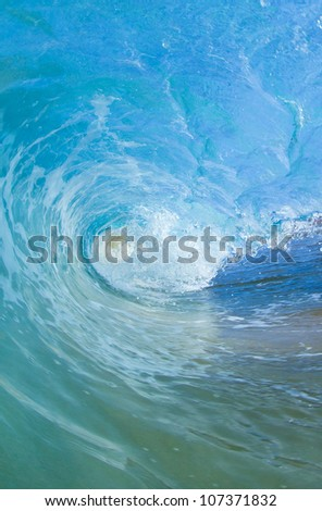 Blue wave breaking into a tube or barrel - stock photo