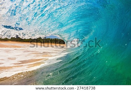 Blue Wave Breaks onto Beach, View from inside the Tube - stock photo