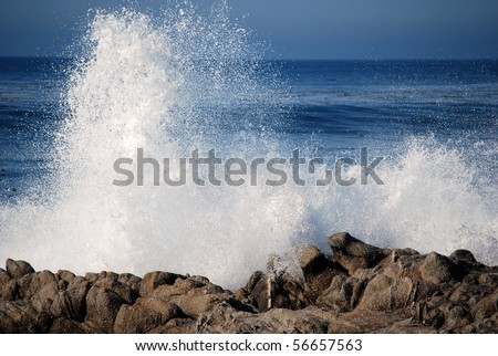 Blue waves crashing on a rocky shore - stock photo