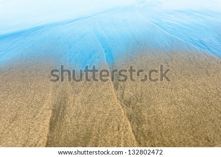 Blue waves on beautiful sandy beach. Ripple on surface of sea. Seabed through transparent water at coastline. Swimming in crystal clear water. Popular outdoor activity. Concept of summer vacations.