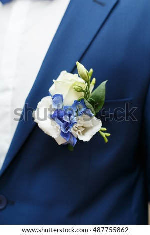 Blue wedding boutonniere on Groom's jacket