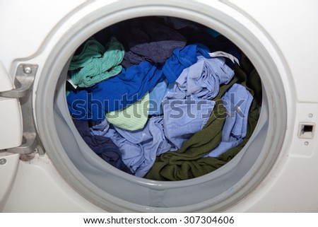 blue wet laundry in washing machine with open lid.
