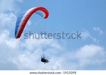 blue, white and red paragliding - stock photo