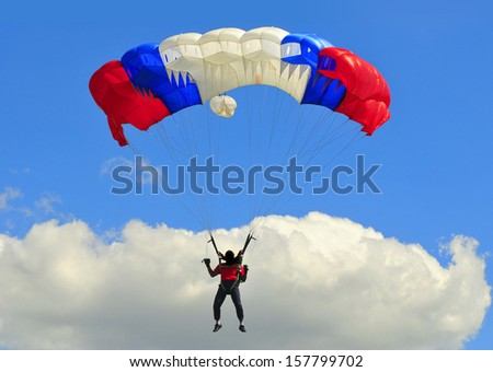 Blue white and red sail parachute on blue sky with white cloud