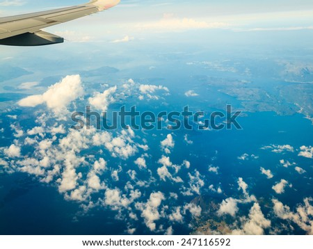 Blue white cloudy sky and plane. View from window of airplane flying in clouds over Norway Scandinavia. Skyscape cloudscape. - stock photo