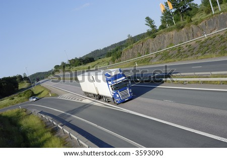 blue-.white truck speeding on highway, countryside in background - stock photo