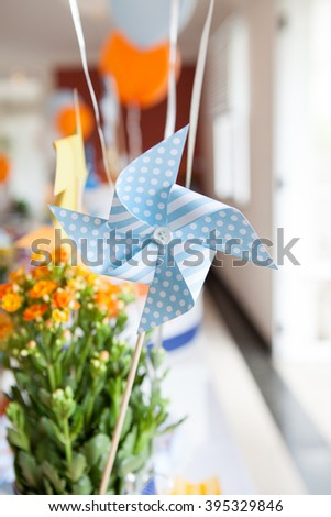 Blue windmill toy and small flowers on birthday party - stock photo