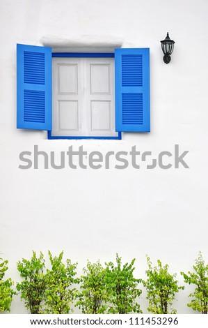 Blue window on white wall - stock photo