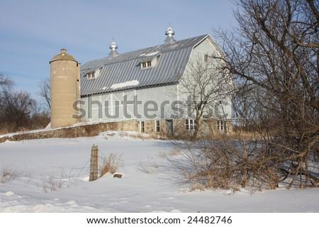 Blue wisconsin dairy barn under blue skies in winter - stock photo