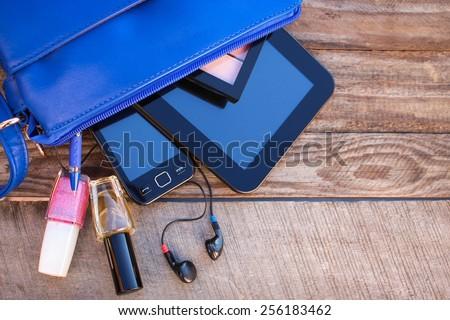 Blue women's purse. Things from open lady handbag. - stock photo