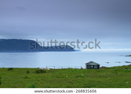 Blue wooden cabin on the shore in Nordic landscape - stock photo