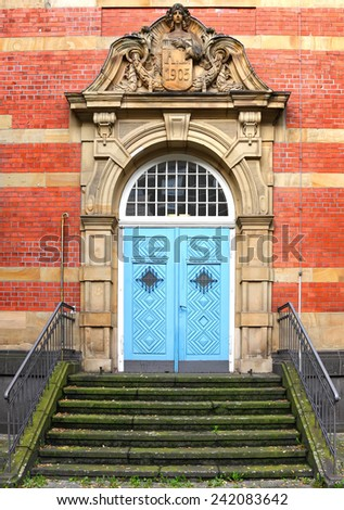 Blue wooden glass door of an old red brick classical building. Renaissance style building - entrance door and stairway. Europe. Architectural theme.  - stock photo