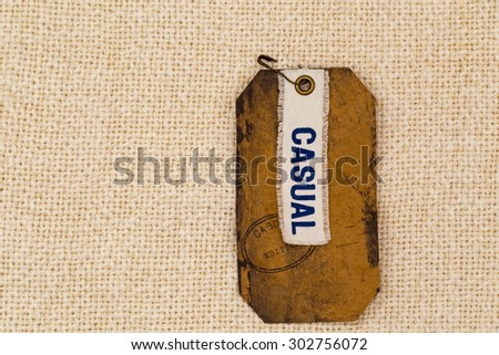 Blue  word CASUAL on a white rag on a rumpled brown paper label  with brown pin on natural white burlap texture background  - stock photo