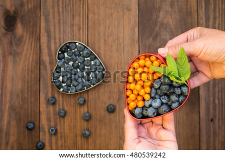 Blueberries and buckthorn in a box in his arms. Wooden fon.Sverhu view. Close-up