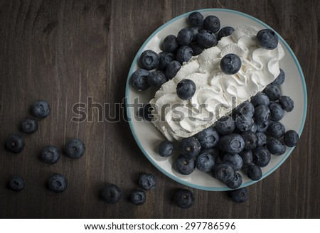 Blueberries and cream on the table - stock photo