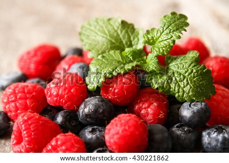 blueberries and raspberries on a stone background - stock photo