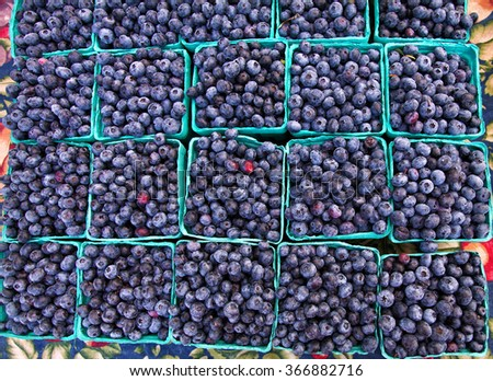Blueberries fresh in crates at farmers market for sale in summer viewed looking down on table - stock photo