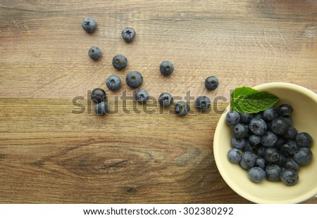 Blueberries in a bowl on a wooden background