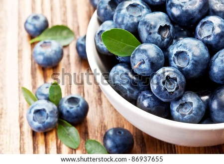 Blueberries in a bowl on a wooden table. - stock photo