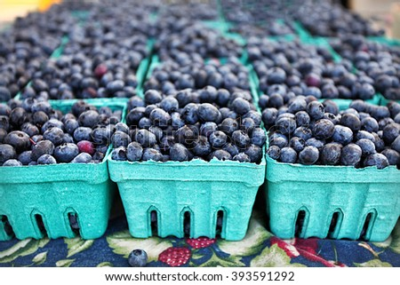 Blueberries in crates at farmers market farm fresh organic fruit in the summer for sale with depth of field - stock photo