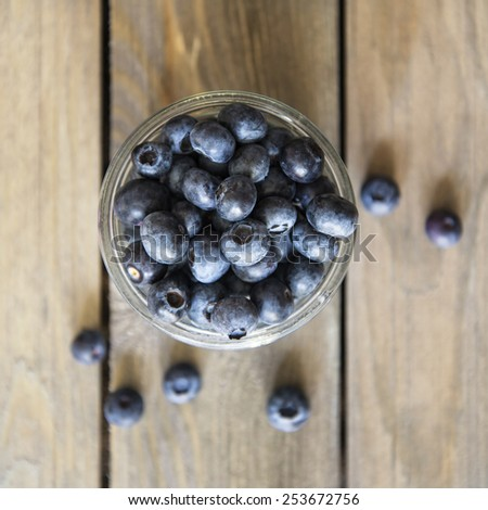 Blueberries in rustic setting with old wooden background - stock photo
