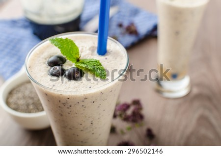 Blueberries milk shake with orange juice on the bottom of glass - stock photo