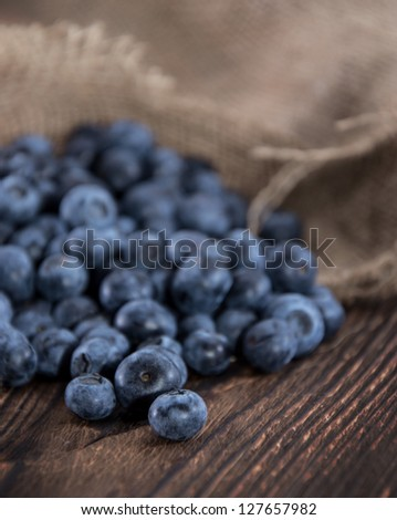 Blueberries on an old wooden table (macro shot)