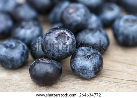 Blueberries on wooden table; focus on single blueberry (Shallow DOF) - stock photo