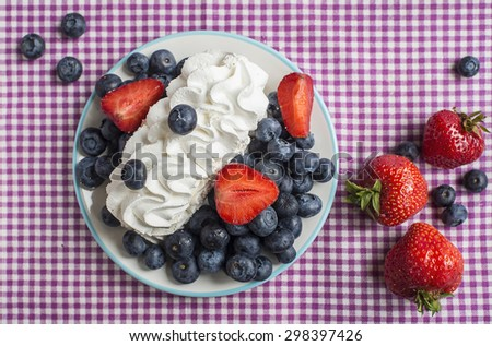 Blueberries, strawberries and cream on the table - stock photo