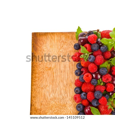 blueberries, strawberry,  raspberries and cherry on a wooden tray  isolated on white background - stock photo