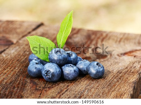 Blueberries with green leaves on a old wooden table - stock photo